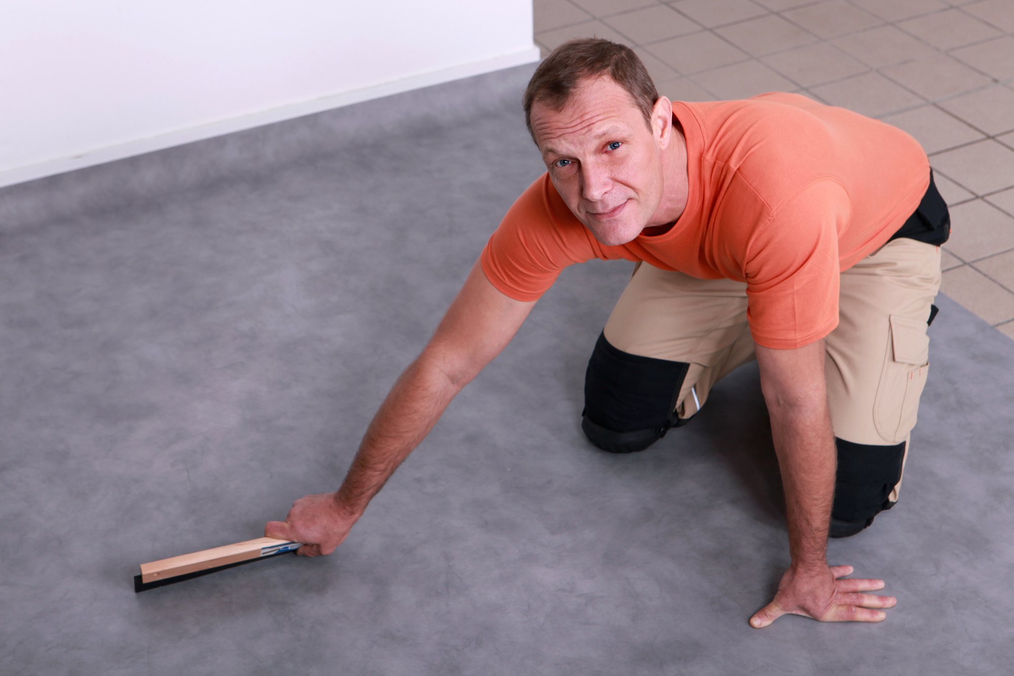 Man installing linoleum flooring