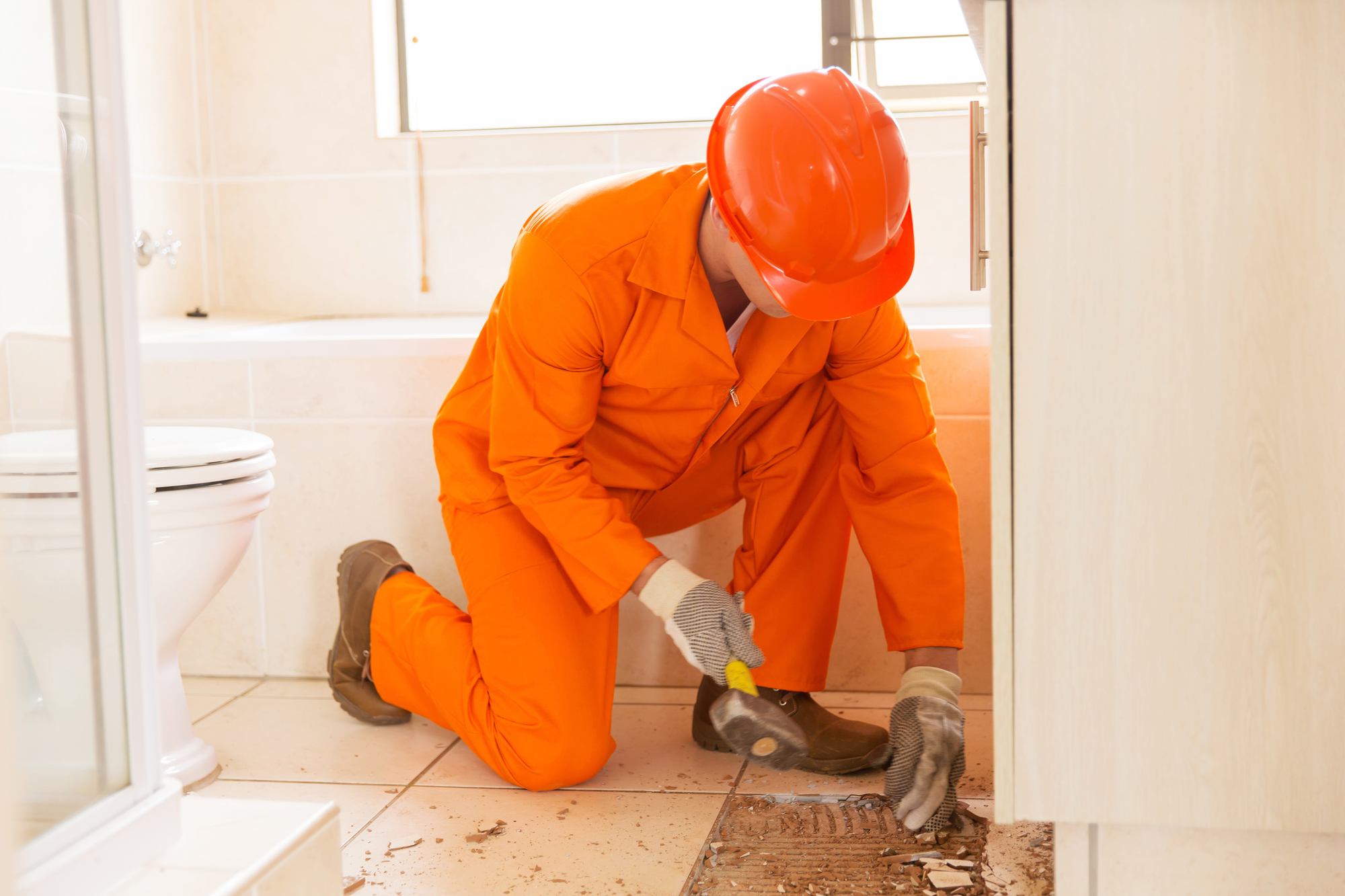 Man in safety gear removing tile floor