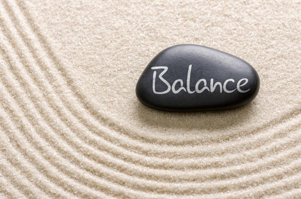 Inscription of the words balance on a black stone