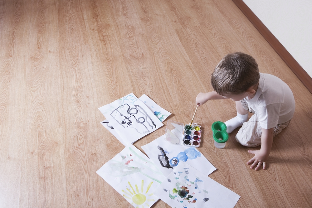 Young child with paintbox sitting on laminate flooring