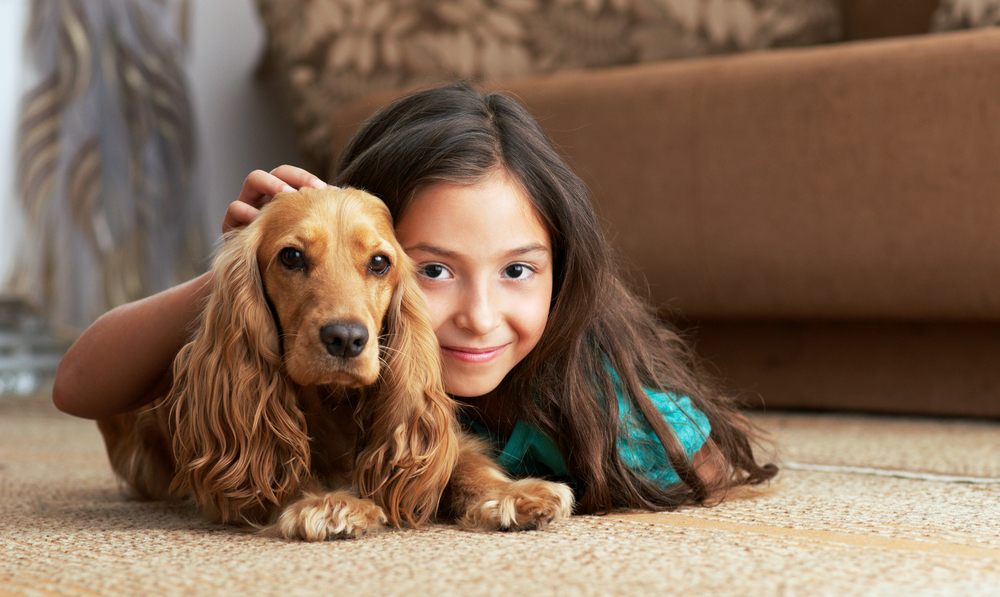 Young girl and dog on cork flooring in a living room